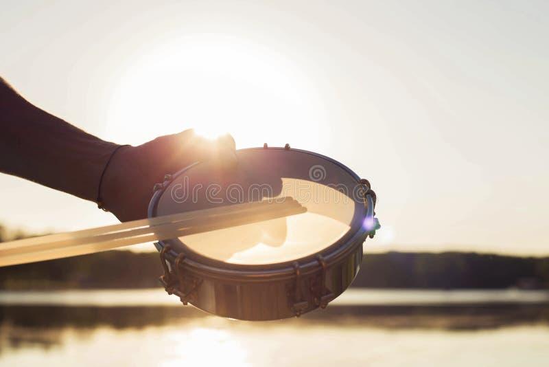 Jouer un tambour de basque d'instrument de musique sur le ciel de fond au coucher du soleil photos stock