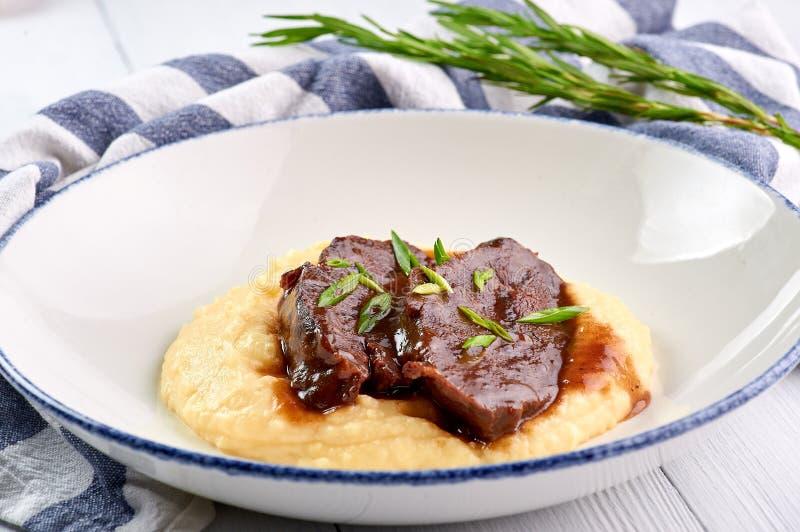 Joues de porc en sauce à Demiglas avec de la purée de pommes de terre Carrillada de cerdo en sauce glace à demi photo libre de droits