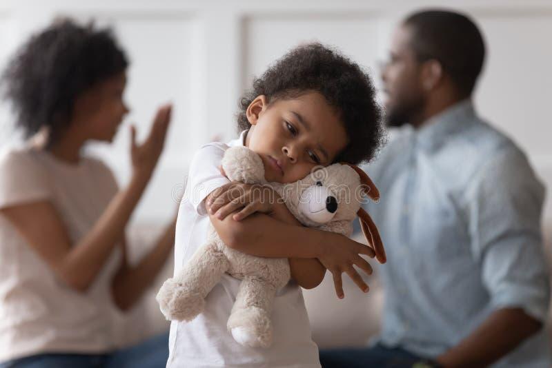 Jouet africain triste d'étreinte de garçon d'enfant contrarié par l'argumentation de parents image stock