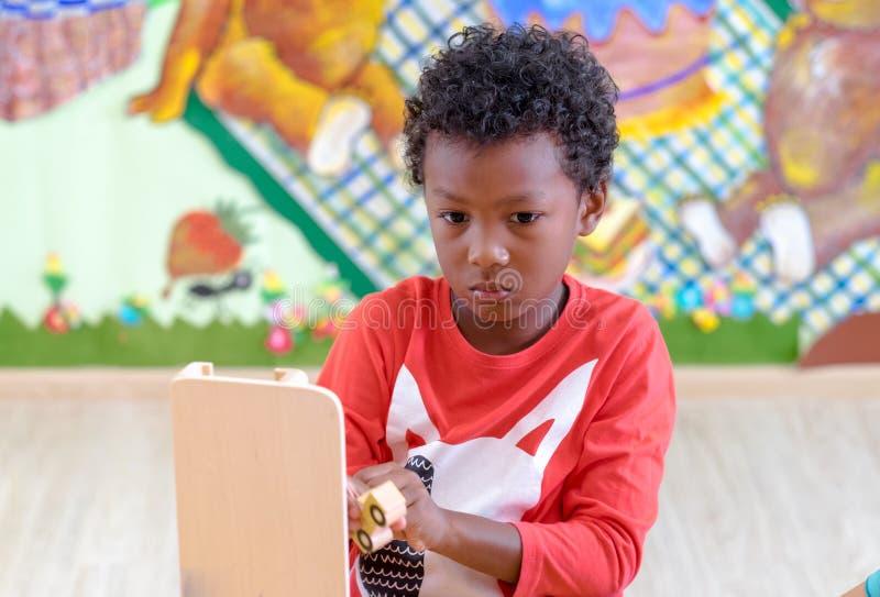 Jouet américain noir de voiture de jeu d'enfant à la salle de classe dans le jardin d'enfants pré photographie stock