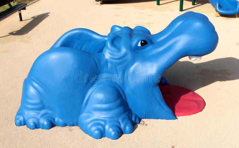 Jouet bleu et rouge coloré d'hippopotame sur le terrain de jeu des enfants photos libres de droits