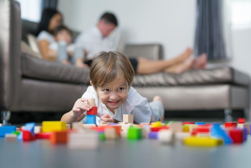 Jouet boisé de jeu caucasien de garçon dans le salon dans la maison avec son fa image libre de droits
