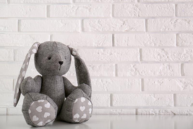 Jouet bourré de lapin pour l'intérieur de pièce de bébé sur la table près du mur de briques photos libres de droits