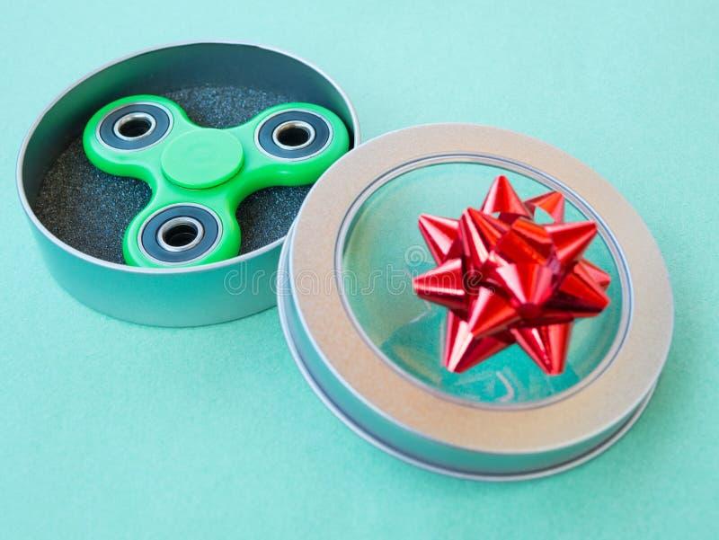 Jouet coloré populaire de fileur de personne remuante dans un boîte-cadeau sur un fond coloré photo stock