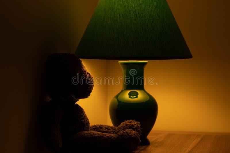 Jouet croustillant attendant sous une lampe ombrage la lumière photo stock