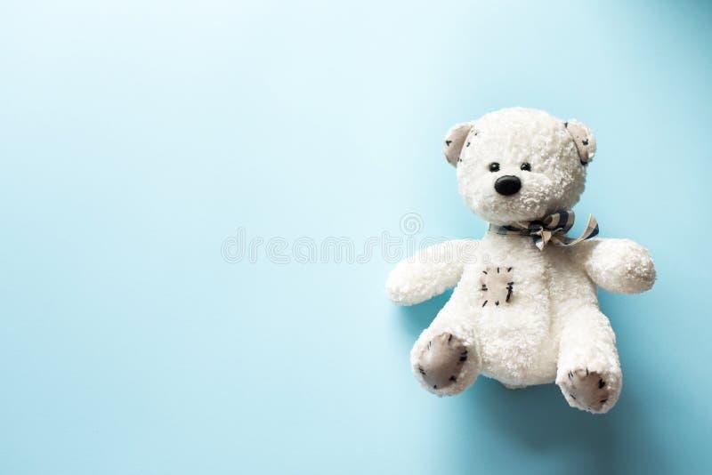 Jouet d'enfant d'ours de nounours sur le fond en pastel de bleus layette avec l'espace de copie photographie stock libre de droits