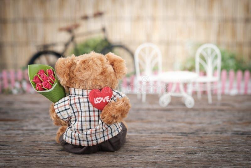 Jouet de chasse à l'ours brun tenant une fleur de rose rouge photos libres de droits
