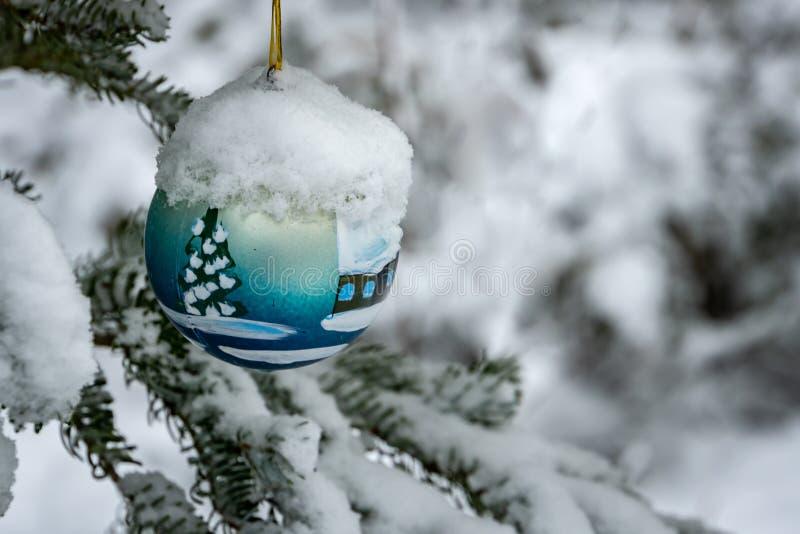 Jouet de Noël, boule bleue de Noël sous la neige sur une branche de sapin du côté gauche Vrai hiver dans le jardin photos libres de droits