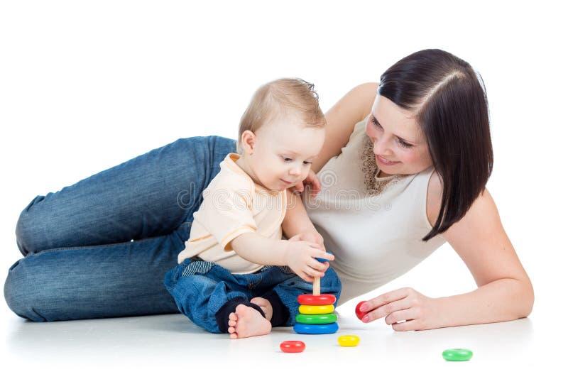 Jouet de pyramide de jeu de mère et de bébé garçon photographie stock libre de droits