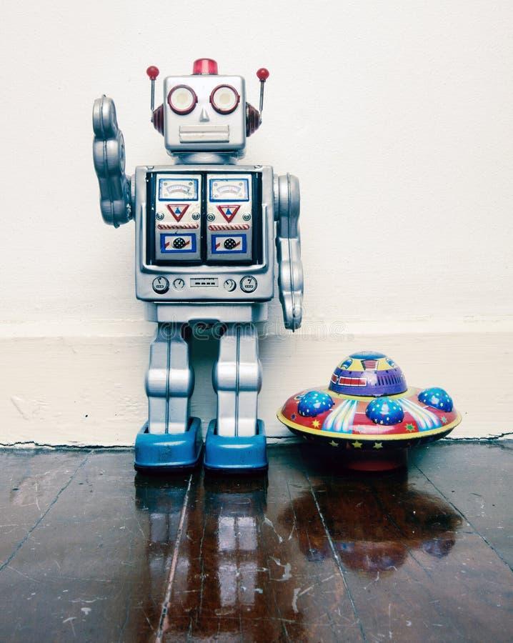 Jouet de robot de vintage avec un UFO de jouet sur un vieux plancher en bois photo stock