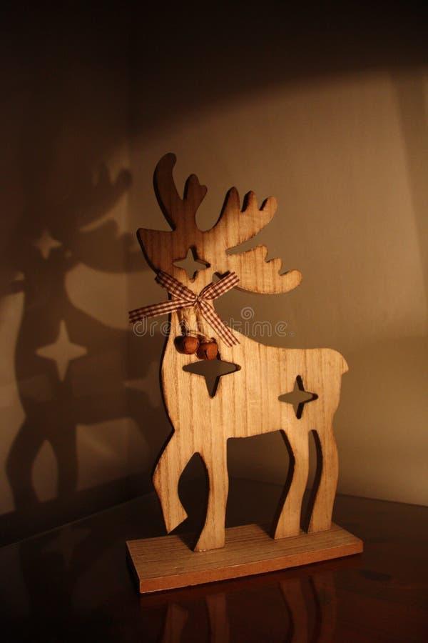 Jouet en bois de Noël de cerfs communs sur la table avec la lumière de la lampe et de l'ombre photo libre de droits