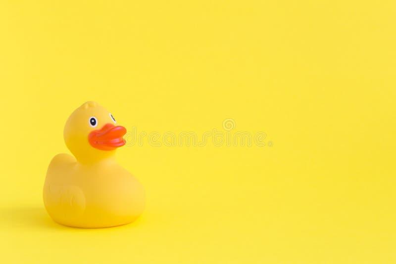 Jouet en caoutchouc de canard pour nager sur le fond jaune image libre de droits