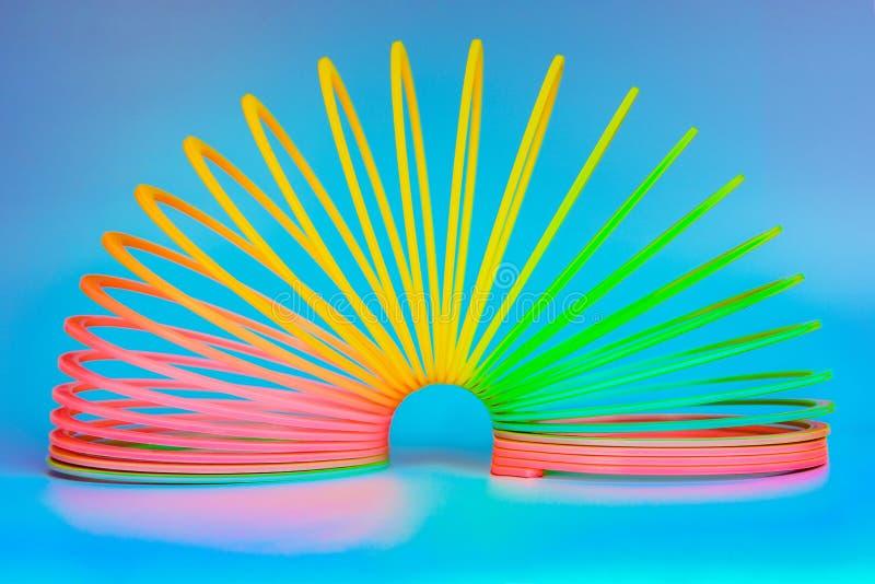Jouet furtif et en plastique avec des couleurs de l'arc-en-ciel, le ressort des enfants colorés sur un fond bleu photographie stock