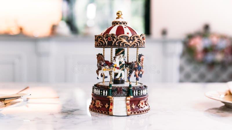 Jouet miniature de carrousel au-dessus de la table supérieure de marbre blanche avec le fond de tache floue image libre de droits