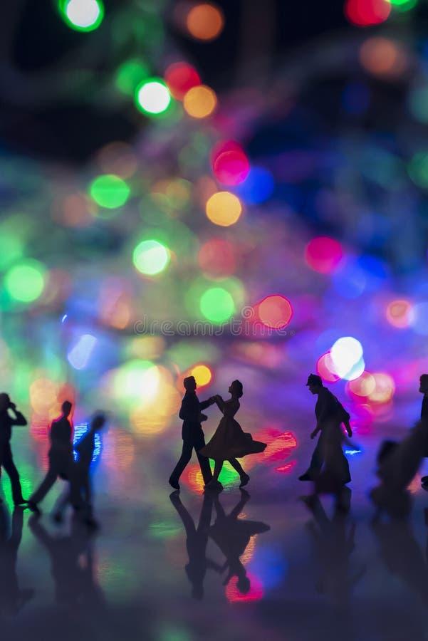 Jouet miniature - Un couple dansant dans la rue, ensemble, parmi les gens de la banlieue très occupés, avec des lumières de boule photo stock