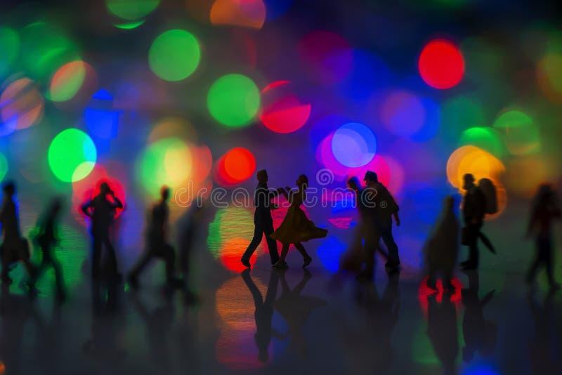 Jouet miniature - Un couple dansant dans la rue, ensemble, parmi les gens de la banlieue très occupés, avec des lumières de boule photos stock