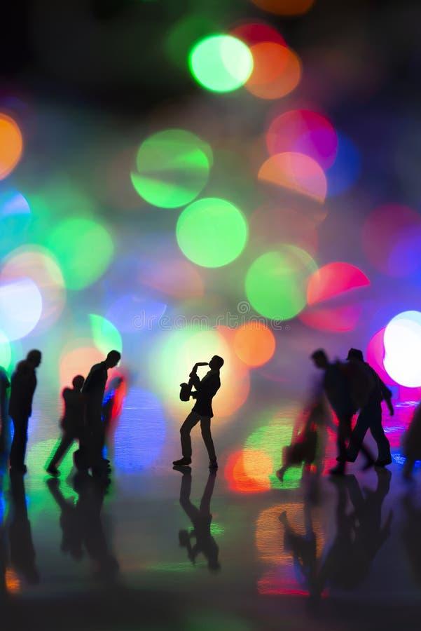 Jouet miniature - Un homme soufflant du saxophone dans la rue avec des lumières de boules colorées parmi les navetteurs très fréq photos stock