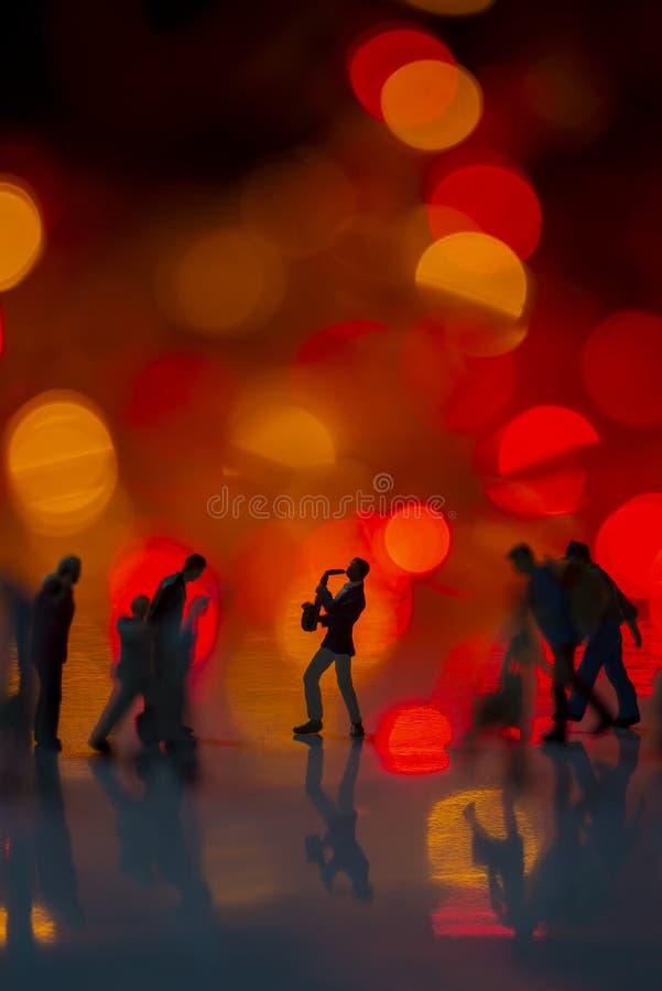 Jouet miniature - Un homme soufflant du saxophone dans la rue avec des lumières de boules colorées parmi les navetteurs très fréq images stock