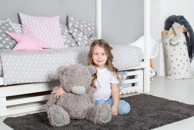 Jouet pr?f?r? L'enfant de fille s'asseyent sur l'ours de nounours d'?treinte de lit dans sa chambre ? coucher L'enfant disposent  photos stock