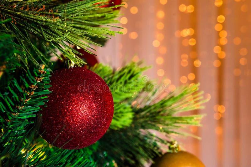 Jouet rouge lumineux de Noël accrochant sur un arbre vert photographie stock libre de droits