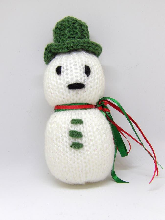 Jouet tricoté du ` s d'enfant de bonhomme de neige avec le chapeau vert et l'écharpe de ruban d'isolement sur le fond blanc photographie stock libre de droits