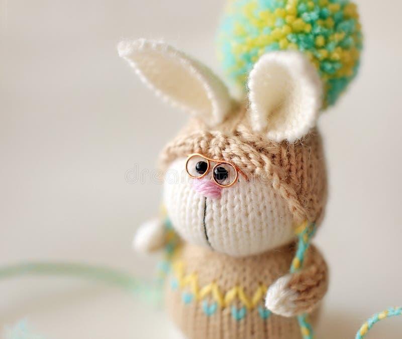 Jouet tricoté fait main Lapin de Pâques avec des verres dans le chandail et le chapeau beiges avec la grande fin de pompon  image stock