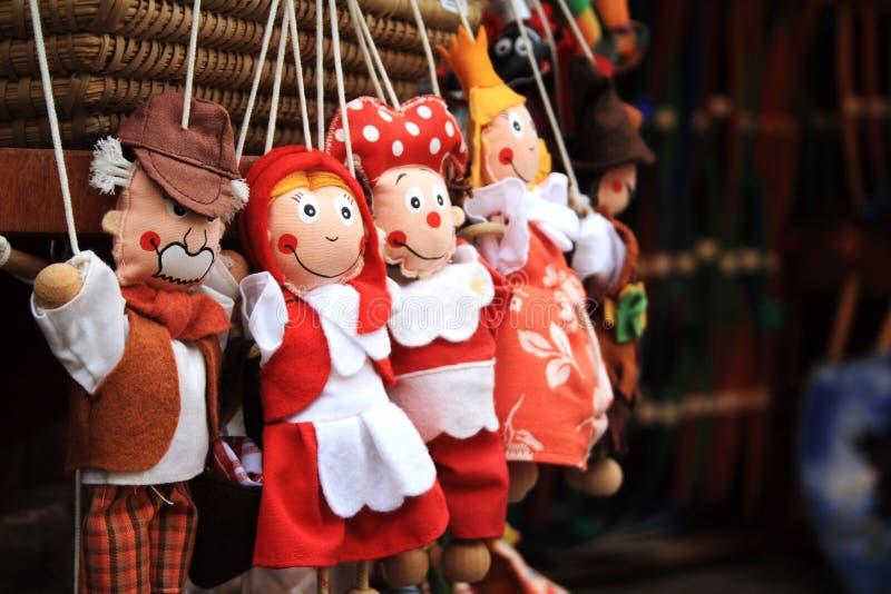 Jouets bourrés dans des vêtements rouges accrochant dans le magasin dans la République Tchèque image stock