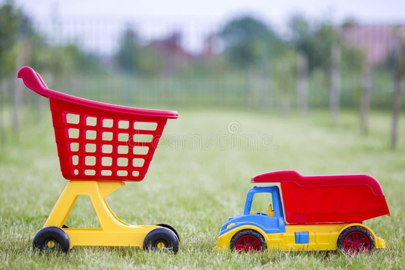 Jouets colorés en plastique lumineux pour des enfants dehors le jour ensoleillé d'été Camion de voiture et chariot de achat images stock