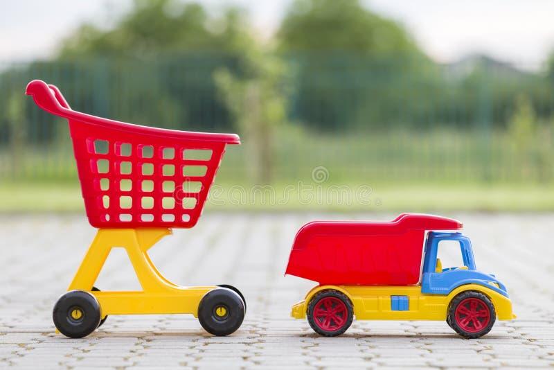 Jouets colorés en plastique lumineux pour des enfants dehors le jour ensoleillé d'été Camion de voiture et chariot de achat image libre de droits