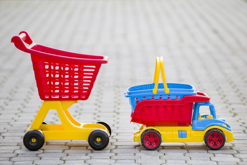 Jouets colorés en plastique lumineux pour des enfants dehors le jour ensoleillé d'été Camion de voiture, panier et chariot de ach images stock