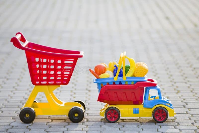 Jouets colorés en plastique lumineux pour des enfants dehors le jour ensoleillé d'été Panier de transport de camion de voiture av images stock