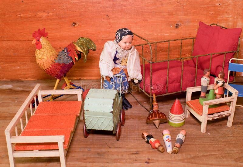 Jouets de vintage pour des filles Rétros jouets en bois Jouez le lit, le chariot de jouet et la rétro poupée Simulacres en bois d image libre de droits