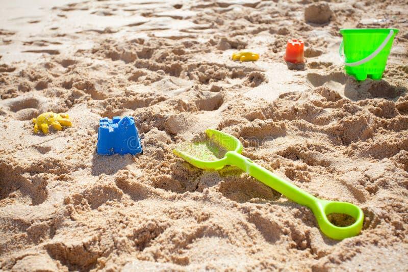 Jouets, pelle et position de sable image stock