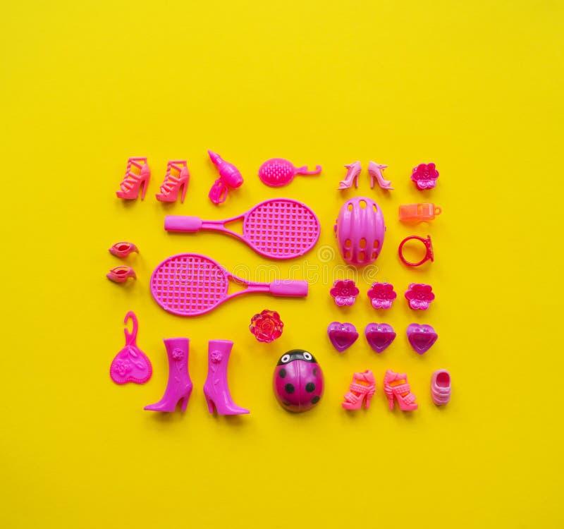 Jouets pour des filles Le rose plat de configuration joue sur un fond jaune image stock