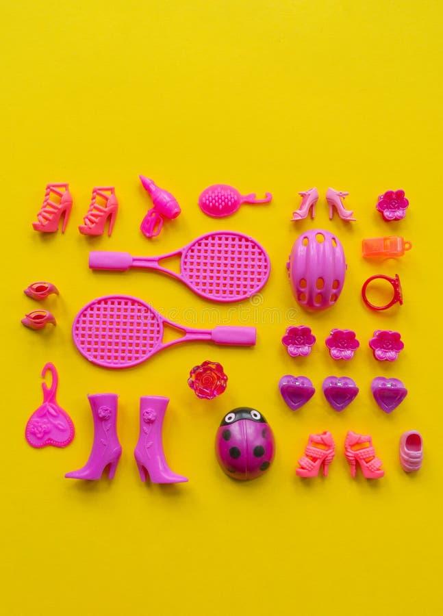Jouets pour des filles Le rose plat de configuration joue sur un fond jaune photographie stock libre de droits