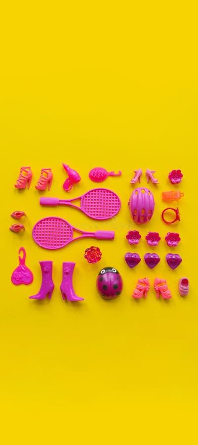 Jouets pour des filles Le rose plat de configuration joue sur un fond jaune photos stock