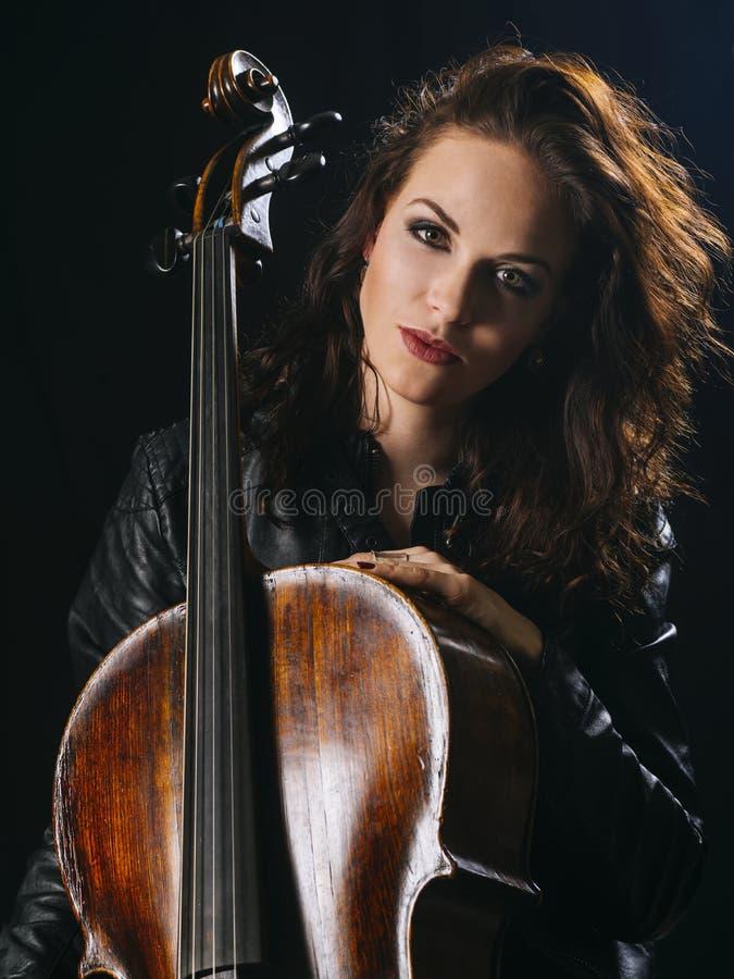 Joueur attirant de violoncelle et son instrument images libres de droits