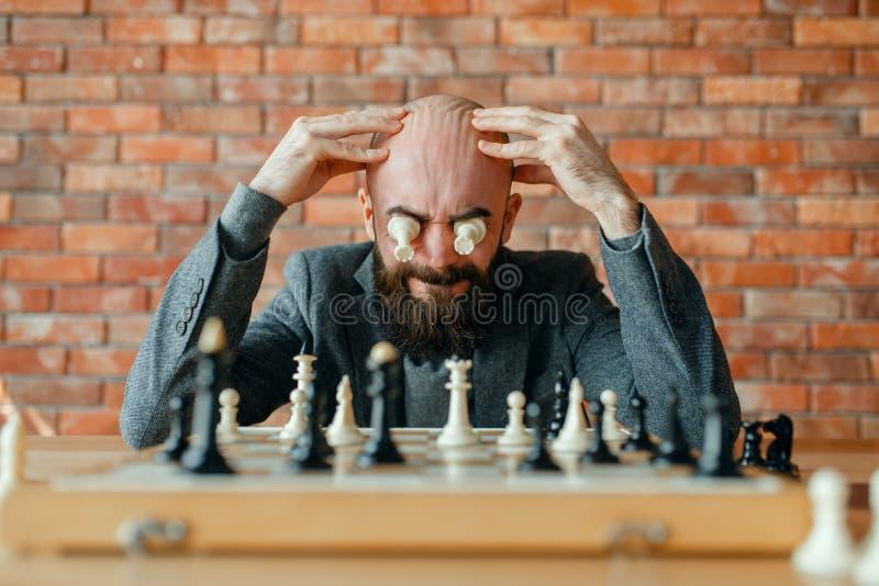 Joueur d'échecs masculin avec des figures dans les yeux photographie stock