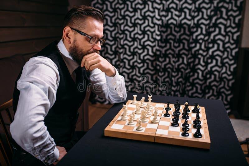 Joueur d'échecs songeur pensant à la stratégie de jeu photographie stock libre de droits