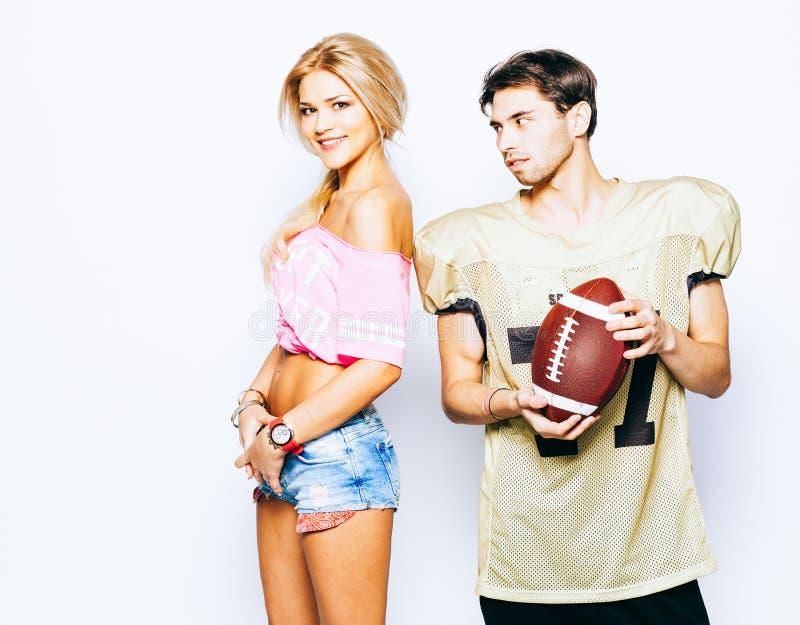 Joueur d'homme de football américain avec la belle majorette de fille posant dans l'uniforme, boule photos stock