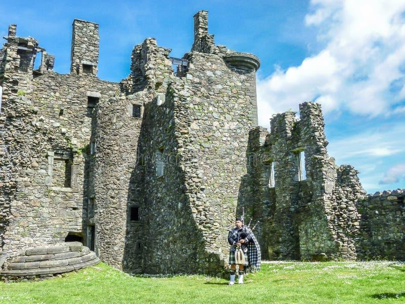 Joueur de cornemuse écossais traditionnel aux ruines du château de Kilchurn image libre de droits