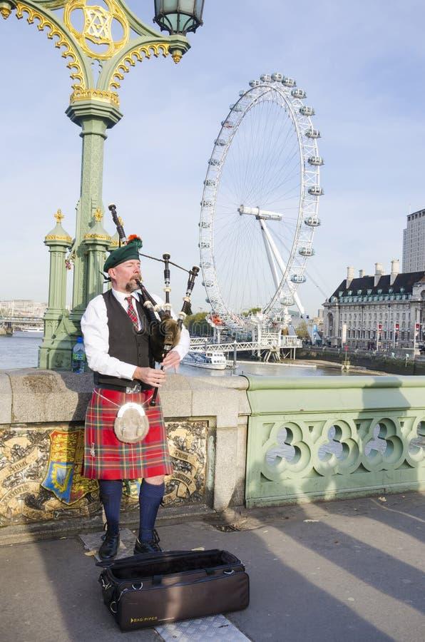 Joueur de cornemuse non identifié sur le pont de Westminster à Londres photos stock