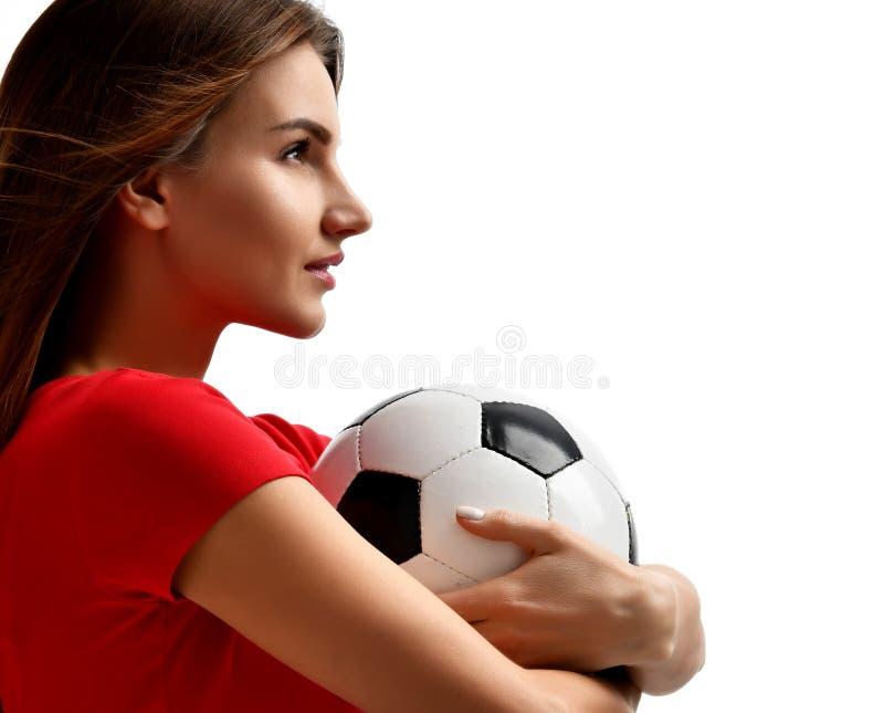Joueur de femme dans le ballon de football uniforme rouge de prise célébrant regardant la composition faisante le coin en plan ra photographie stock