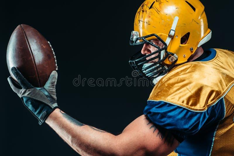 Joueur de football américain avec la boule lacée dans des mains photos libres de droits