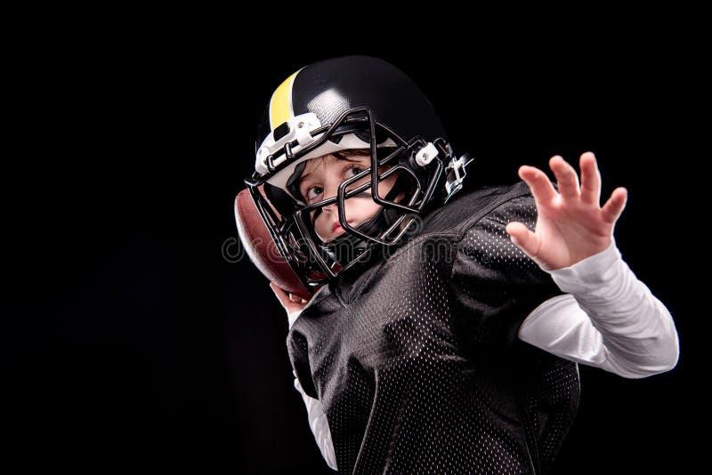 Joueur de football américain de petit garçon dans la boule de lancement uniforme images libres de droits