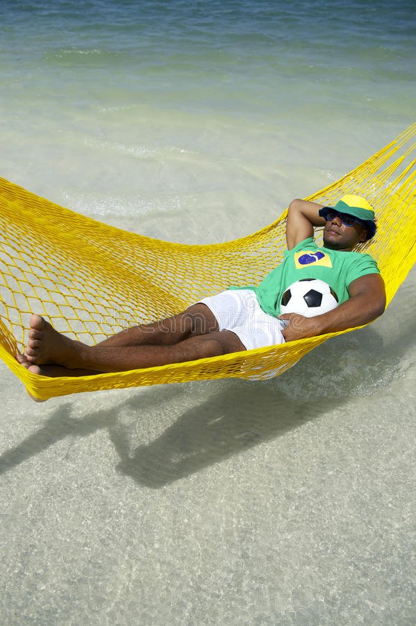 Joueur de football brésilien détendant dans l'hamac de plage photographie stock