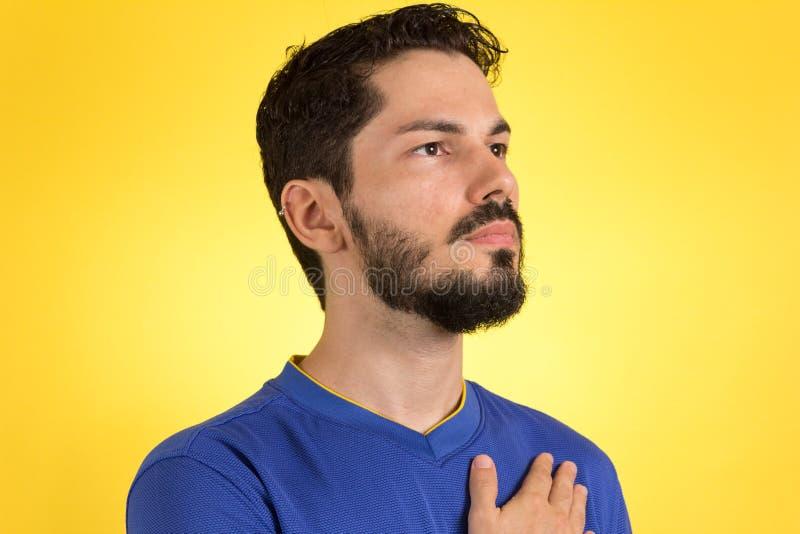 Joueur de football brésilien du football écoutant l'hymne et le Han images stock