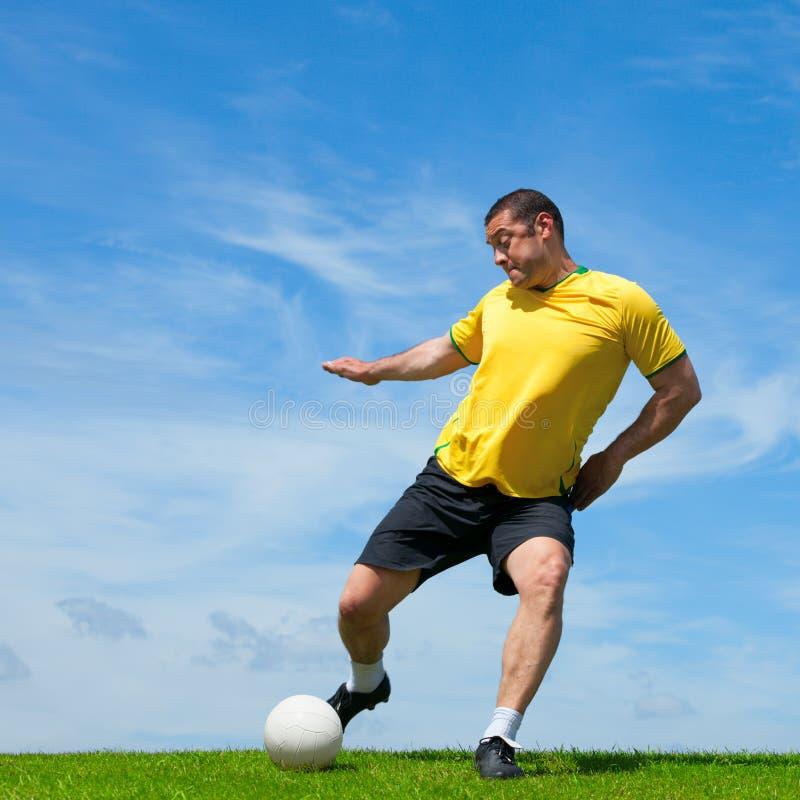 Joueur de football brésilien du football donnant un coup de pied une boule photographie stock