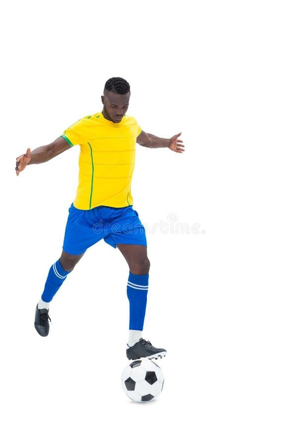 Joueur de football dans la boule de coup de pied jaune images libres de droits