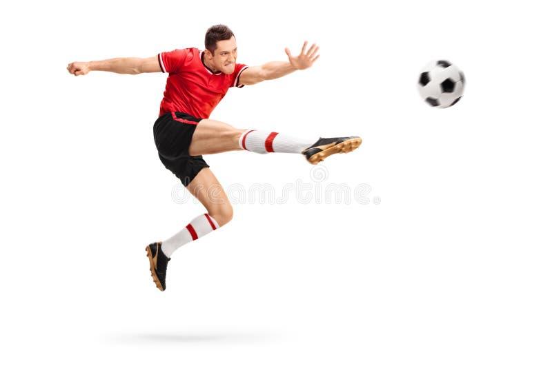 Joueur de football donnant un coup de pied une boule dans l'entre le ciel et la terre image libre de droits